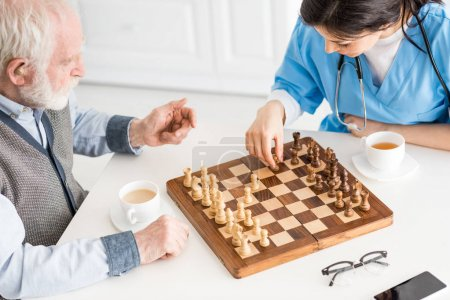 Photo for High angle view of nurse with senior man sitting on kitchen, playing in chess - Royalty Free Image