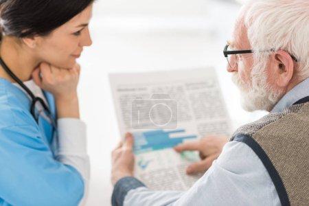 Photo pour Concentration sélective de l'homme aux cheveux gris parlant avec l'infirmière, tenant le journal dans les mains - image libre de droit