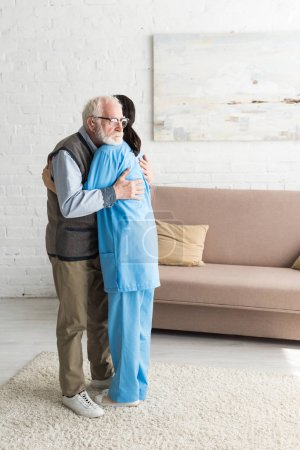 Photo for Calm senior man hugging with nurse, standing in bright room - Royalty Free Image