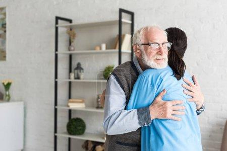 Photo pour Homme retraité heureux étreignant avec le docteur, restant dans la salle lumineuse - image libre de droit