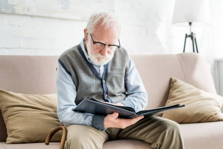 Photo for Senior man sitting on sofa, and holding photo album in hands - Royalty Free Image