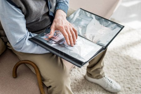 Photo for Cropped view of senior man holding photo album in hands - Royalty Free Image