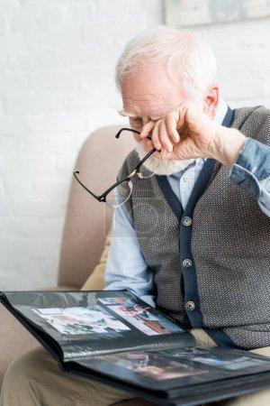 Photo pour Bouleversé l'homme aux cheveux gris pleurant, et tenant l'album de photo dans les mains - image libre de droit