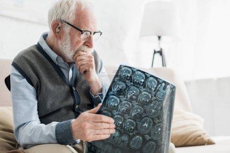Photo pour Homme aîné concentré dans des lunettes regardant l'image de rayon x - image libre de droit