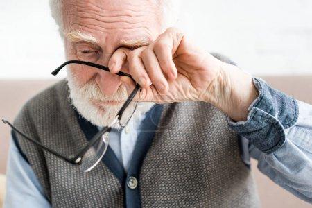 Photo pour Homme aîné triste retenant des glaces, et couvrant l'oeil de sa main - image libre de droit