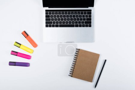 Foto de Vista superior de la computadora portátil, resaltadores coloridos, cuaderno y pluma en blanco - Imagen libre de derechos