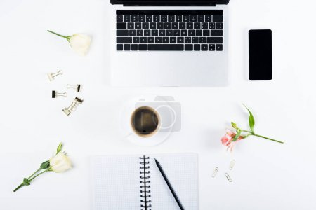 Photo for Top view of laptop and smartphone with blank screen, notebook with pen, paper clips, binder clips, flowers and cup of coffee on white - Royalty Free Image