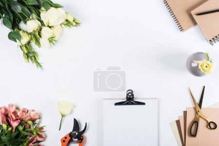 Photo pour Vue du dessus du presse-papiers, des sécateurs, des fleurs, des carnets, des ciseaux et du papier artisanal sur blanc - image libre de droit