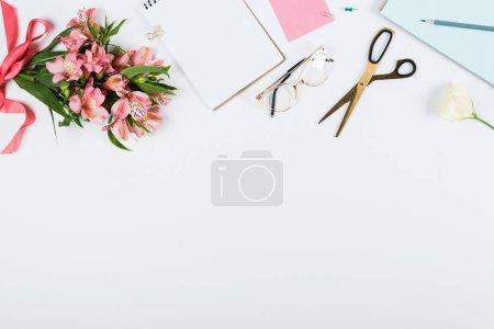 Photo pour Vue de dessus des fleurs avec ruban, presse-papiers, ciseaux, cahier, crayon et lunettes sur blanc - image libre de droit