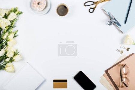 Photo pour Vue du haut des fleurs, tasse de café, carte de crédit, beignet, ciseaux, presse-papiers, verres, papier d'artisanat et livre sur le blanc - image libre de droit