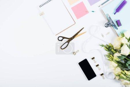 Photo pour Vue du haut du carnet, papiers, ciseaux, fleurs, ruban, surligneur et presse-papiers sur blanc - image libre de droit
