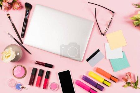 Foto de Vista superior de la computadora portátil, teléfono inteligente con pantalla en blanco, tarjeta de crédito, gafas, flores y cosméticos decorativos en rosa - Imagen libre de derechos