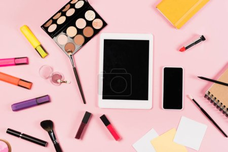 Foto de Top view of digital tablet and smartphone with blank screen, notebooks and decorative cosmetics on pink - Imagen libre de derechos