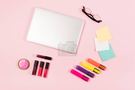 Photo for Top view of laptop, glasses, highlighters and decorative cosmetics on pink - Royalty Free Image
