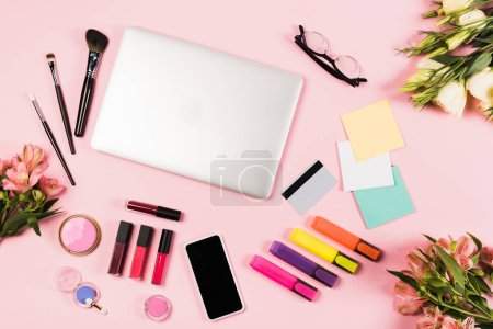 top view of laptop, smartphone with blank screen, credit card, flowers, glasses, highlighters and decorative cosmetics on pink