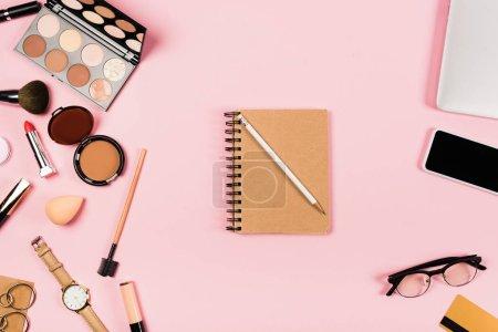 Photo pour Vue du haut du carnet avec crayon, lunettes, smartphone avec écran vierge, carte de crédit, accessoires et cosmétiques décoratifs sur rose - image libre de droit