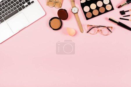 Photo pour Vue de dessus de l'ordinateur portable, montre-bracelet, lunettes et cosmétiques décoratifs sur rose - image libre de droit