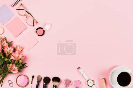 Photo pour Vue supérieure de tasse de café, fleurs, cosmétiques décoratifs et accessoires sur le rose - image libre de droit