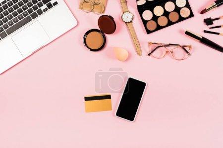 Photo pour Vue du haut de l'ordinateur portable, smartphone avec écran blanc, carte de crédit et cosmétiques décoratifs sur le rose - image libre de droit