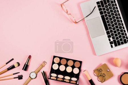 Photo pour Vue du haut de l'ordinateur portatif, des accessoires et des cosmétiques décoratifs sur le rose - image libre de droit