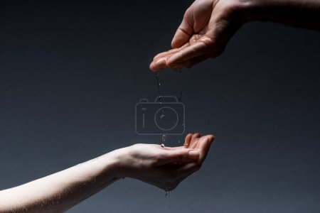 Photo for Cropped view of man and woman with water drops on dark - Royalty Free Image
