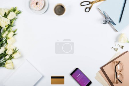 KYIV, UKRAINE - MAY 11, 2019: top view of cup of coffee, doughnut, credit card, flowers, glasses, scissors, clipboard and smartphone with instagram app on screen on white