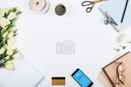 Photo pour KYIV, UKRAINE - MAY 11, 2019: top view of cup of coffee, doughnut, credit card, flowers, glasses, scissors, clipboard and smartphone with skype app on screen on white - image libre de droit