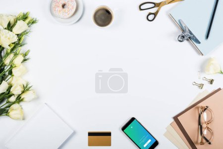 Foto de KYIV, UKRAINE - MAY 11, 2019: top view of cup of coffee, doughnut, credit card, flowers, glasses, scissors, clipboard and smartphone with twitter app on screen on white - Imagen libre de derechos