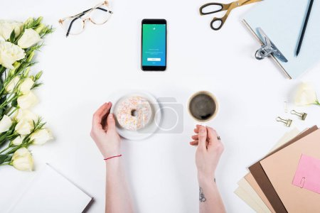 Photo for KYIV, UKRAINE - MAY 11, 2019: cropped view of woman with cup of coffee, doughnut and smartphone with twitter app on screen at workplace - Royalty Free Image
