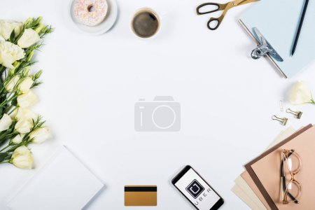 Photo pour KYIV, UKRAINE - MAY 11, 2019: top view of cup of coffee, doughnut, credit card, flowers, glasses, scissors, clipboard and smartphone with uber app on screen on white - image libre de droit