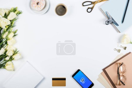 Photo pour KYIV, UKRAINE - MAY 11, 2019: top view of cup of coffee, doughnut, credit card, flowers, glasses, scissors, clipboard and smartphone with shazam app on screen on white - image libre de droit