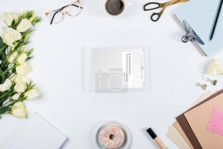 Photo for KYIV, UKRAINE - MAY 11, 2019: top view of cup of coffee, doughnut, flowers, glasses, book, papers, clipboard and digital tablet with vk app on screen on white - Royalty Free Image