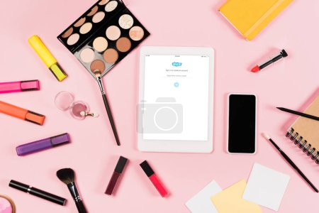 Photo pour KYIV, UKRAINE - MAY 11, 2019: top view of digital tablet with skype app on screen, smartphone with blank screen, highlighters and decorative cosmetics on pink - image libre de droit