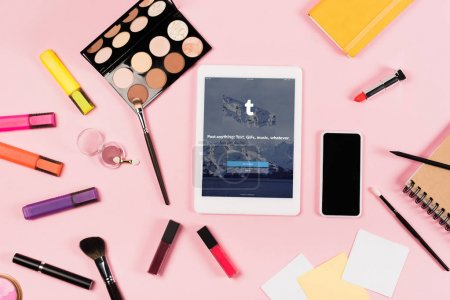 Photo pour KYIV, UKRAINE - MAY 11, 2019: top view of digital tablet with tumblr app on screen, smartphone with blank screen, highlighters and decorative cosmetics on pink - image libre de droit
