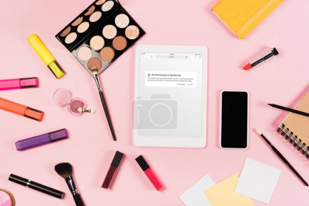 KYIV, UKRAINE - MAY 11, 2019: top view of digital tablet with vk app on screen, smartphone with blank screen, highlighters and decorative cosmetics on pink