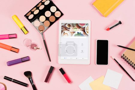 Photo for KYIV, UKRAINE - MAY 11, 2019: top view of digital tablet with foursquare app on screen, smartphone with blank screen, highlighters and decorative cosmetics on pink - Royalty Free Image