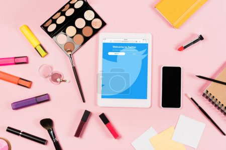Photo pour KYIV, UKRAINE - MAY 11, 2019: top view of digital tablet with twitter app on screen, smartphone with blank screen, highlighters and decorative cosmetics on pink - image libre de droit