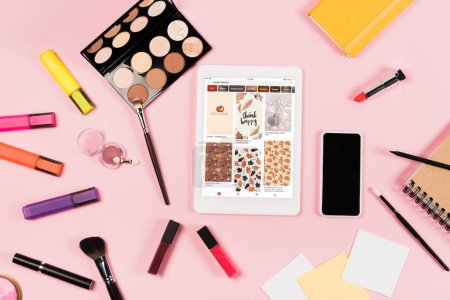 Photo for KYIV, UKRAINE - MAY 11, 2019: top view of digital tablet with pinterest app on screen, smartphone with blank screen, highlighters and decorative cosmetics on pink - Royalty Free Image