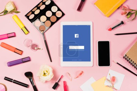 Photo for KYIV, UKRAINE - MAY 11, 2019: top view of digital tablet with facebook app on screen, smartphone with blank screen, flowers, highlighters and decorative cosmetics on pink - Royalty Free Image