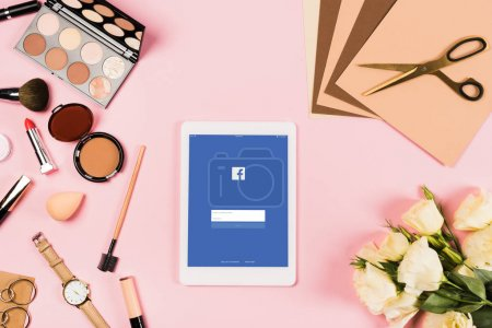 KYIV, UKRAINE - MAY 11, 2019: top view of digital tablet with facebook app on screen, flowers, accessories, decorative cosmetics, scissors and papers on pink