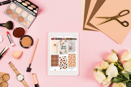 Photo for KYIV, UKRAINE - MAY 11, 2019: top view of digital tablet with pinterest app on screen, decorative cosmetics, flowers, craft paper and scissors on pink - Royalty Free Image