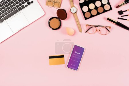 Photo for KYIV, UKRAINE - MAY 11, 2019: top view of laptop, decorative cosmetics, glasses, wristwatch, credit card and smartphone with instagram app on screen on pink - Royalty Free Image