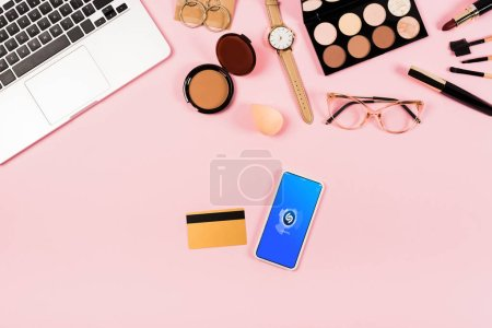 KYIV, UKRAINE - MAY 11, 2019: top view of laptop, decorative cosmetics, glasses, wristwatch, credit card and smartphone with shazam app on screen on pink