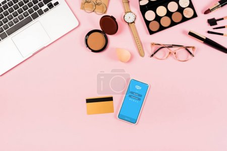 KYIV, UKRAINE - MAY 11, 2019: top view of laptop, decorative cosmetics, glasses, wristwatch, credit card and smartphone with skype app on screen on pink