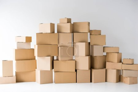 Photo for Brown cardboard boxes stacked on each other on white - Royalty Free Image