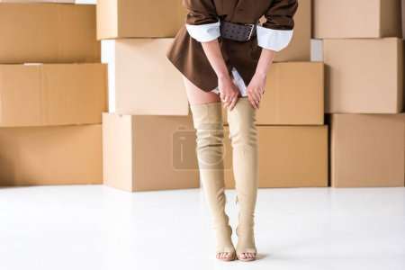 Photo pour Vue recadrée de fille touchant des bottes tout en restant près des boîtes sur le blanc - image libre de droit