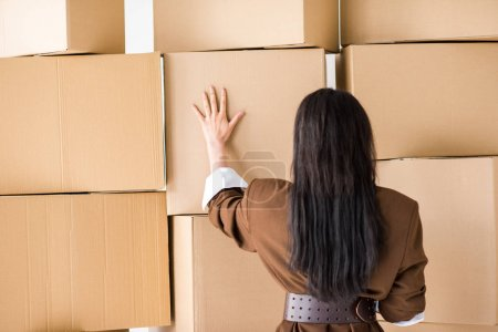 Photo for Back view of brunette girl standing and touching box - Royalty Free Image
