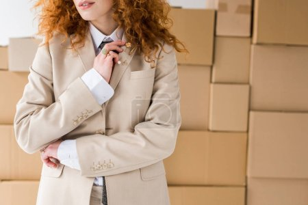 Photo for Cropped view of curly redhead girl standing near boxes on white - Royalty Free Image