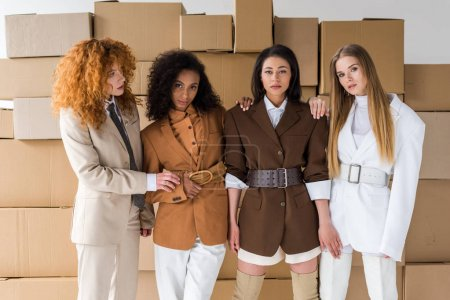 Photo pour Beautiful multicultural women posing near boxes on white - image libre de droit