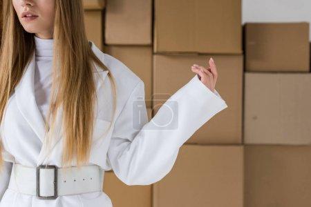 Foto de Vista recortada de la niña de pie cerca de cajas de cartón marrón - Imagen libre de derechos